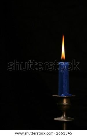 Flame of blue candle in the darkness