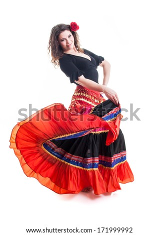 Flamenco dancer in beautiful red dress with rose in the hair. Photo in movement