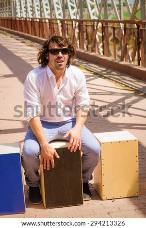 Flamenco musician with an assortment of cajon instruments - stock photo