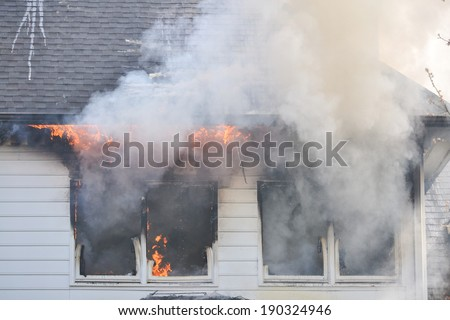 Flames are evident through the windows of a burning house during a training fire  - stock photo