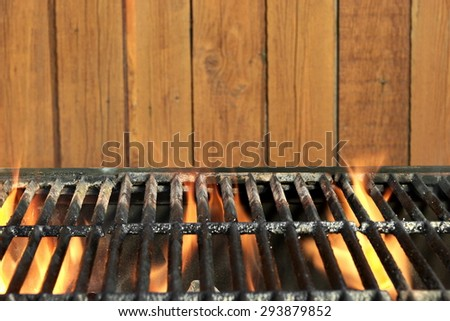 Flaming BBQ Charcoal Cast Iron Grill Close-up And Brown Wood Siding Wall In  The Background. Cookout or Picnic or Summer Outdoor Party Concept And Idea, With Copy Space - stock photo
