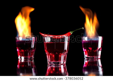 flaming cocktail with pepper on a black background - stock photo