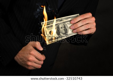 Flaming money in hand - stock photo
