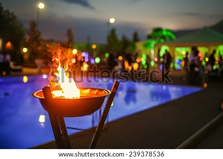 Flaming torch at sunset by the pool - stock photo