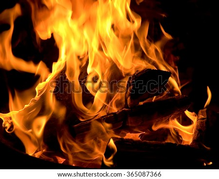 Flaming wood fire against black background; Particulate emissions caused by wood-fired ovens - stock photo