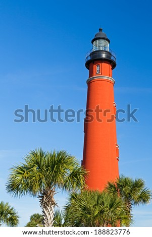 Flanked by palms, the brilliant red lighthouse at Florida's Ponce de Leon Inlet (formerly Mosquito Inlet) has stood watch over the Atlantic Ocean since 1887 and is the tallest in the state. - stock photo
