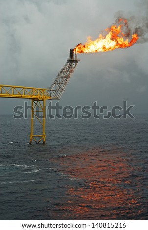 Flare boom nozzle and fire on offshore oil rig - stock photo