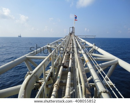 Flare or Vent boom on a remote oil&gas production platform with blue sky. - stock photo