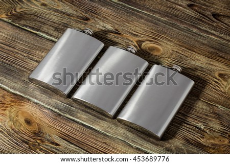 Flask alcoholic beverage on wooden background