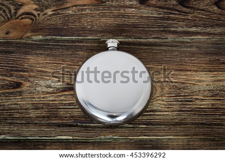 Flask brutal alcoholic beverage on wooden background - stock photo