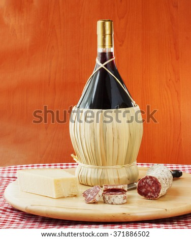 Flask of red wine with cheese and sausage, vertical image - stock photo