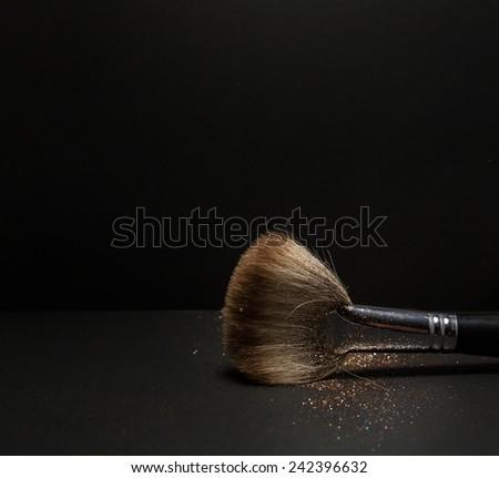 Flat blush brush with blush on it, loose powder blush, isolated on black backgrownd. - stock photo