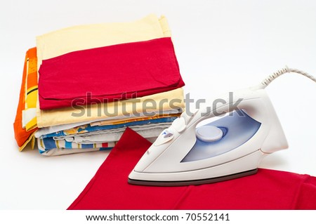 Flat electric iron and clothes on white background - stock photo