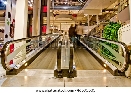 flat escalator with people in the shopping mall - stock photo