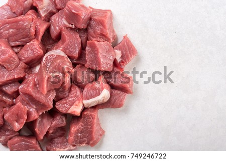 Flat lay above chopped raw beef steak on the white marble background with copy space.