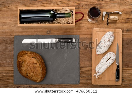 flat lay above view of dry sausage delicatessen sliced meat with wine and traditional bread on wooden board