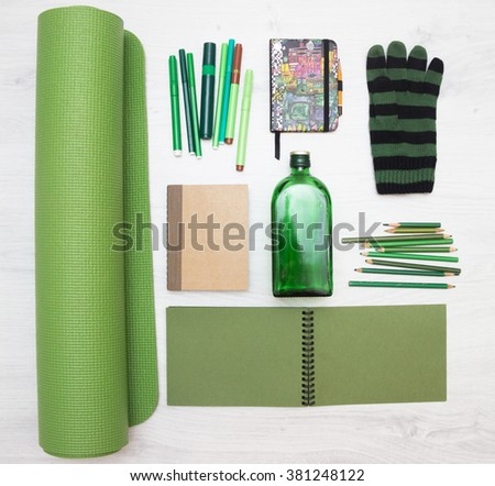 flat lay brown and green objects. Yoga carpet, felt pens, pencils, bottle, notebooks and glove. - stock photo