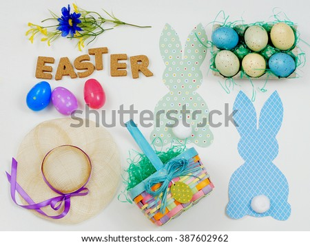 Flat lay design for Easter in pretty spring colors of green, yellow, blue, pink and purple includes flowers, a bonnet, bunny cutouts, Easter eggs, a colorful basket and cork letters.
