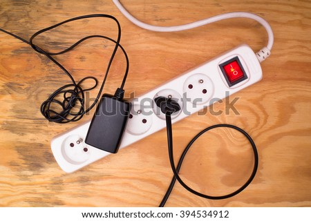 Flat lay - extension cord and plugged cables and devices on wooden floor - stock photo
