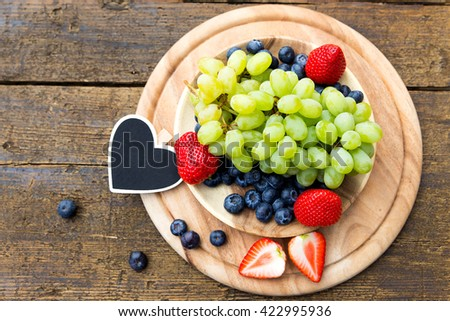flat lay, fresh fruits with a heart slate on wooden table, copyspace, grapes, blueberries and strawberries - stock photo