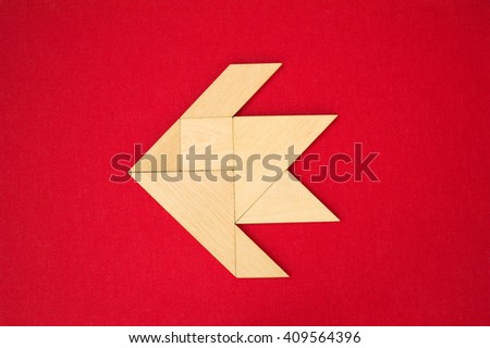 Flat lay - geometrical abstract background or arrow showing direction made of wooden tangram pieces. Unicolor background made of red fabric texture. Vignetting.  - stock photo