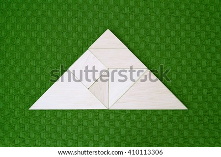 Flat lay - geometrical abstract background or arrow showing direction made of wooden tangram pieces. Unicolor background made of green fabric texture. Vignetting.  - stock photo