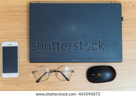 Flat lay object laptop with glasses and cellphone on old wooden table