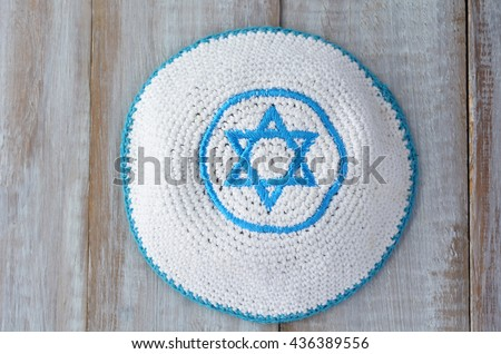 Flat lay of a Knitted kippah with embroidered blue and white Star of David on a wooden table. Jewish lifestyle concept copy space - stock photo