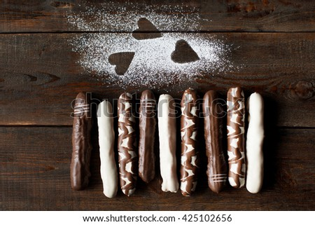 Flat lay of chocolate cookies with sugar powder hearts on dark wooden background. Close up of white, dark and decorated chocolate cake sticks top view. Some free space - stock photo