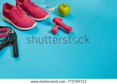 Flat lay of dumbbell, bottle of water, jump rope and sneaker, sport equipments, fitness items, top view