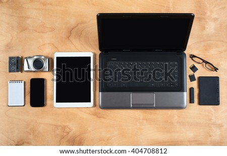 Flat lay of personal office accessories, laptop, notebook, coffee cup  and camera on wood background, top view - stock photo