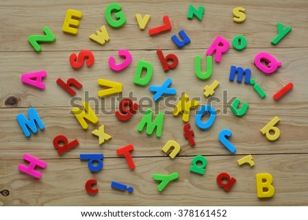 Flat lay of scattered English letters on a wooden background. Language education concept - stock photo