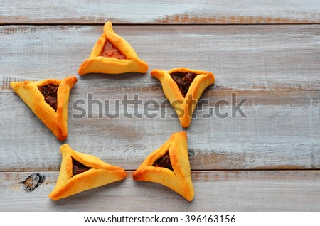 Flat lay of Star of David made out of Purim Cookies - Hamentashen (Ozen Haman) for Purim Jewish Holiday. Copy space - stock photo