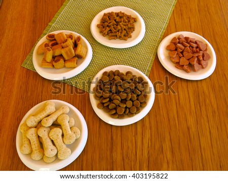 Flat lay: pet food on wood table. Tasty delicious dog snacks! Love your dog and take care of it - stock photo