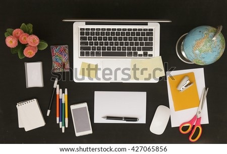 Flat lay photo of office desk with laptop and and lots of stationery objects - stock photo