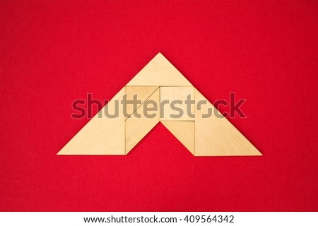 Flat lay - pictogram of roof, geometrical abstract background or arrow showing direction made of wooden tangram pieces. Unicolor background made of red fabric texture. Vignetting.  - stock photo