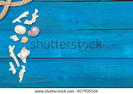 flat lay: seashells and rope on blue boards, copyspace - stock photo