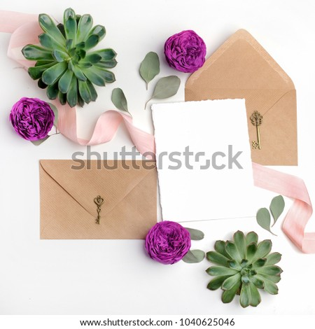 Flat lay shot of letter and eco paper envelope on white background. Wedding invitation cards or love letter with flowers. Valentine's day or other holiday concept. Top view