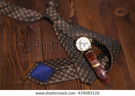 Flat lay shot of Men fashion accessories. Brown watch, tie on wooden background. Still life. Business look.