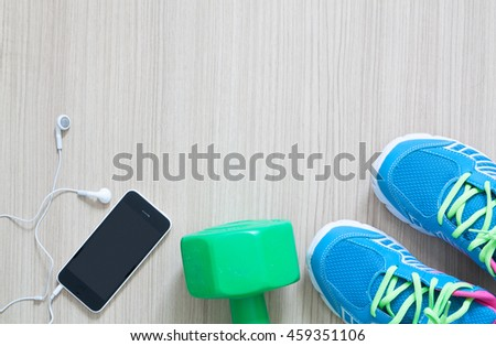 flat lay shot of sport sneakers earphones and phone on wooden background