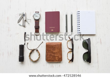 Flat lay, top view, men's accessories and essential travel items on white rustic wooden background