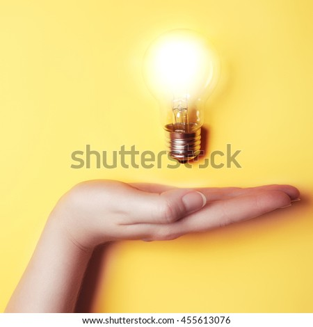 Flat lay. Top View. New idea and business concept with female hand holding light bulb. Creative background. Science background - stock photo