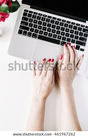 Flat lay, top view office table desk. Workspace with girl's hands, laptop, red roses bouquet, mint diary, coffee mug and golden scissors on white background.