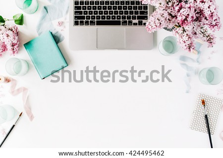 Flat lay, top view office table desk. Workspace with paintbrush, laptop, lilac flowers bouquet, spool with beige and blue ribbon, mint diary on white background.