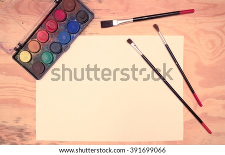 Flat lay - watercolors, paintbrushes, paper, wooden desk (vintage color shift)  - stock photo