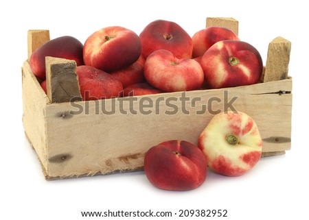 flat nectarines in a wooden crate on a white background - stock photo