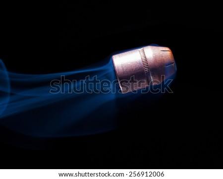 Flat nosed handgun bullet heading up with smoke behind - stock photo