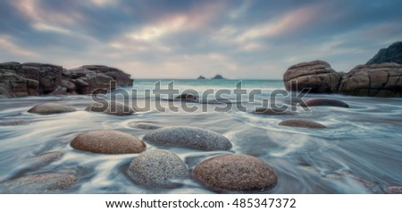 Flat oval stones on a beach with tide rushing over them