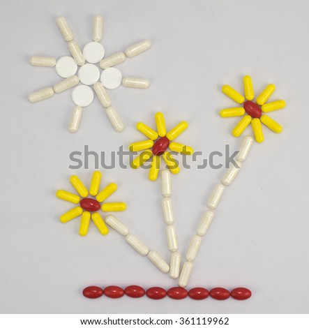 Flat picture of pills and capsules on a grey background - stock photo