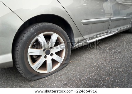 Flat rear tire on a car - stock photo